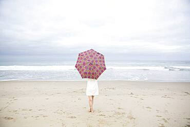Woman standing with umbrella on beach