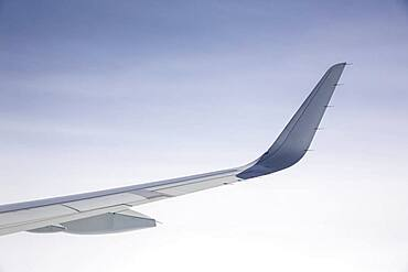 Airplane wing under clear sky