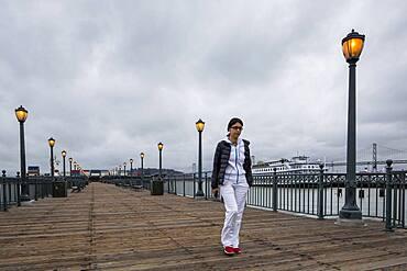 Middle Eastern woman walking on pier