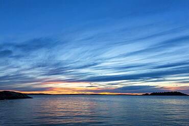 Clouds in sunset sky over still ocean