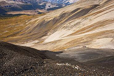 Distant view of hikers walking on remote hillside