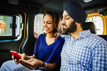 Indian couple using cell phone in taxi