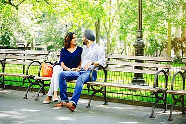 Indian couple sitting on bench in urban park