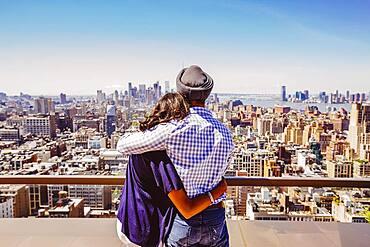 Indian couple admiring New York cityscape, New York, United States