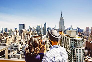 Indian couple taking cell phone photograph of New York cityscape, New York, United States