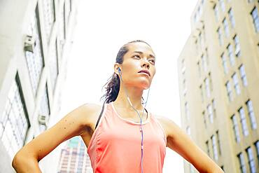 Mixed race athlete listening to earbuds in city
