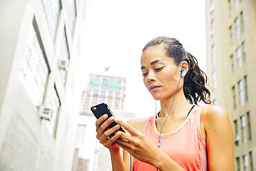 Mixed race athlete listening to mp3 player in city