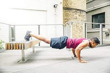 Indian man doing push-ups on bench
