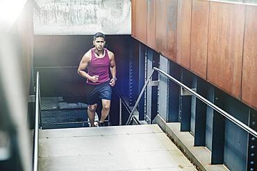 Indian man jogging on city steps