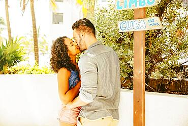 Couple kissing at tourist signs