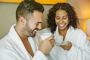 Couple drinking coffee in hotel room