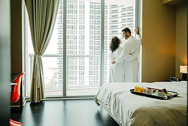 Couple hugging in bathrobes in hotel room