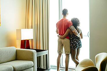Couple hugging and looking out hotel window