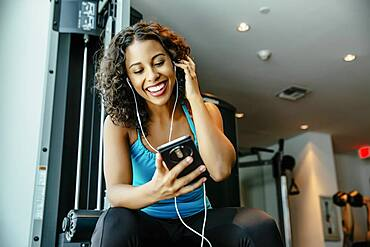 Woman listening to earbuds in gymnasium