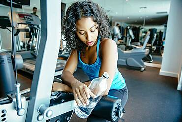 Woman resting on exercise machine in gymnasium