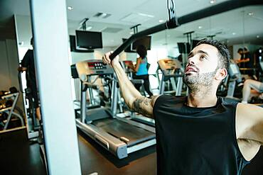 Man using exercise machine in gymnasium