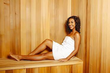 Smiling woman relaxing in sauna