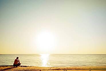 Mixed race man sitting on beach