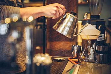 Caucasian barista pouring hot water over coffee in cafe