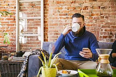 Caucasian man drinking coffee on sofa in living room