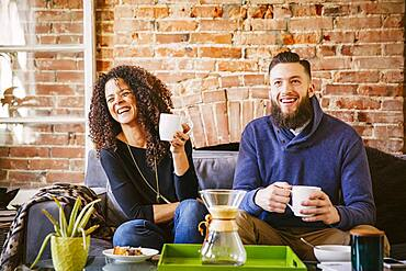 Couple drinking coffee on sofa in living room