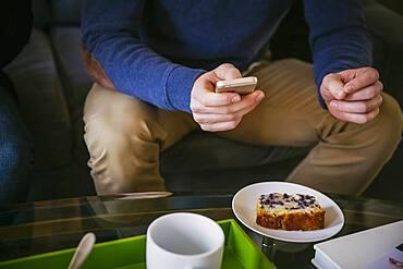 Caucasian man using cell phone at breakfast