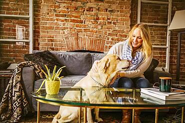 Caucasian woman petting dog in living room
