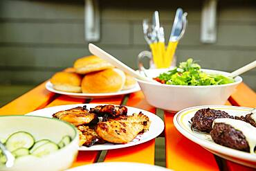 Close up of salad, meat, cucumbers and salad on table