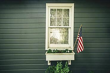 American flag in window box outside house
