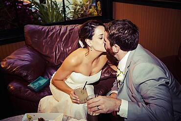 Caucasian bride and groom kissing in living room
