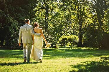 Caucasian bride and groom walking in grass