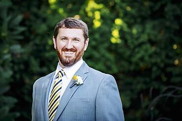 Caucasian groom smiling in garden