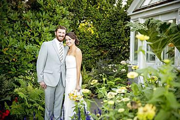 Caucasian bride and groom smiling in garden
