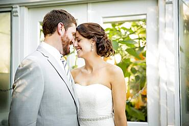 Caucasian bride and groom touching foreheads in garden