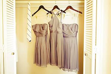Bridesmaid dresses hanging in closet