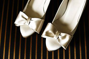 Close up of white high heels with bows