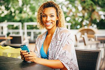 Mixed race teenager using cell phone at table