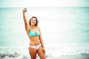 Mixed race teenager taking selfie in bikini on beach