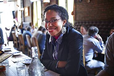 Black woman sitting at restaurant table