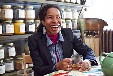 Black woman drinking tea in tea shop