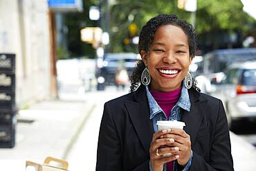 Black woman drinking coffee outdoors