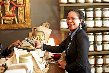 Black woman purchasing tea in tea shop