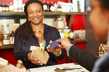 Black woman serving customer in tea shop
