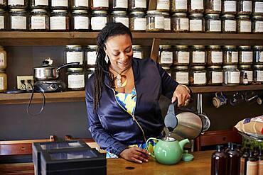 Black woman pouring tea in tea shop
