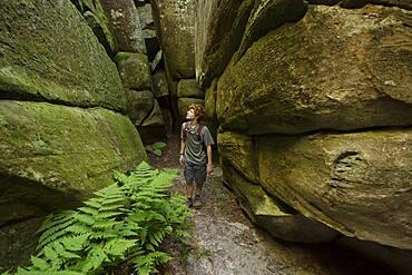 Caucasian teenage boy exploring cave