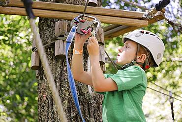 Caucasian boy hooking harness to zip
