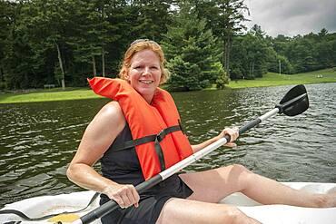 Caucasian woman rowing canoe in lake