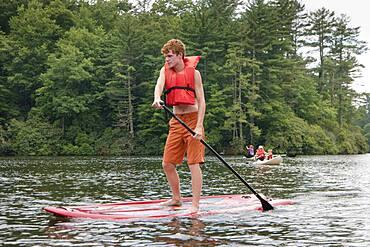 Caucasian teenage boy rowing paddleboat in lake
