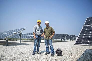 Caucasian technicians standing near solar panels
