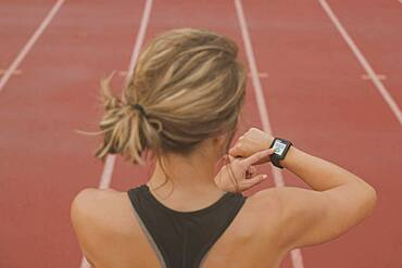Caucasian runner checking watch on sports field